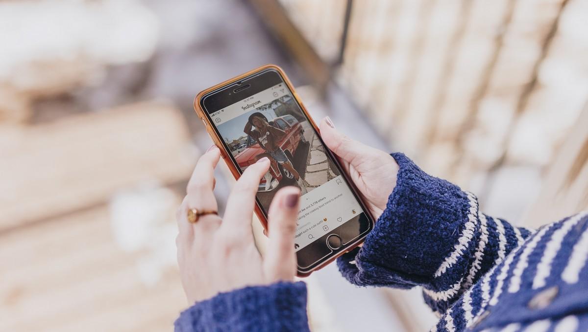 Mladá dívka si prohlíží fotografie v aplikaci Instagram.